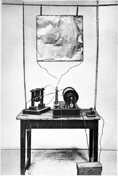 Marconi's first transmitter incorporating a monopole antenna. It consisted of an elevated copper sheet (top) connected to a Righi spark gap (left) powered by an induction coil (center) with a telegraph key (right) to switch it on and off to spell out text messages in Morse code.