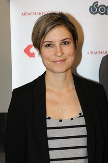 A woman in her twenties with short blonde hair, wearing a black jacket and grey shirt with black stripes.