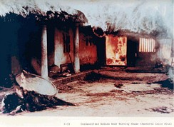 Dead bodies outside a burning dwelling