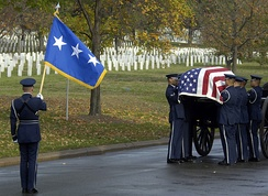 USAF HG Bearers transfer the remains of a lieutenant general from the horse-drawn caisson to the gravesite during a funeral at Arlington National Cemetery.