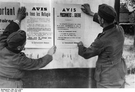 German soldiers posting notices for refugees and prisoners of war in France, May 1940
