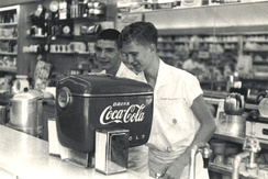 "Claimed to be the first installation anywhere of the 1948 model ""Boat Motor"" styled Coca-Cola soda dispenser, Fleeman's Pharmacy, Atlanta, Georgia. The ""Boat Motor"" soda dispenser was introduced in the late 1930s and manufactured until the late 1950s. Photograph circa 1948."