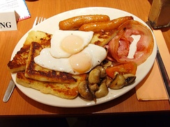 A full Ulster fry served in Belfast, Northern Ireland. The potato bread is under the eggs, with the soda farl at the bottom.
