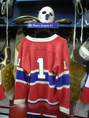 Goaltender Jacques Plante's #1 jersey exhibited at the Hockey Hall of Fame. Over time, the number 1 became less common among players in that position