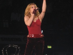 A female blond performer standing on a stage. She is wearing a red top and dark brown pants with a red shiny belt. Her left hand is stretched upwards. She is looking up while holding a microphone on her right hand. Beside her, a chair is visible.