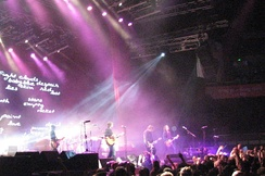 "A wide shot of a stage with only four musicians visible: each is playing a type of guitar. A drum kit is mid-stage but the Coghill is obscured by lighting and equipment. The audience are across the front, below stage, some have one fist raised. A photographer is centred, front of stage, another is further to the right with a camera pointing at the band, a third cameraman is at left pointing into the crowd. Behind the group on the left is a large screen which depicts various words including ""Fight clouds baby blue despair skin red lies lost stars ith empty rocket paint love g"". Overhead lights shine down on the performers. To the right is a large sign with white writing ""bring your living room to life"" on red-orange background."