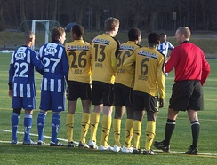 Six players standing in a line, being talked to by another man.