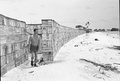 A wind break constructed from ration boxes protects the small RAF camp at Kelai, Maldive Islands, which serves as a refuelling base for flying boats operating in the Indian Ocean.