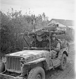 A jeep ambulance of the Royal Canadian Army Medical Corps (R.C.A.M.C.) bringing in two wounded Canadian soldiers on the Moro River front, south of San Leonardo di Ortona, Italy, December 10, 1943