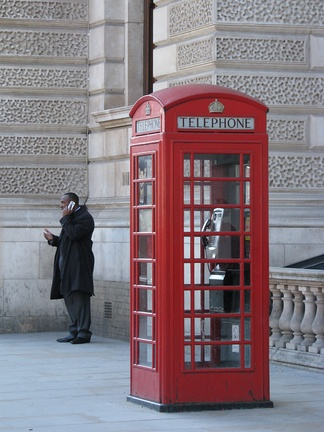 A man talks on his mobile phone while standing near a conventional telephone box, which stands empty. Enabling technology for mobile phones was first developed in the 1940s but it was not until the mid 1980s that they became widely available. By 2011, it was estimated in Britain that more calls were made using mobile phones than wired devices.[1]