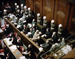 Rare color photo of the trial at Nuremberg, depicting the defendants, guarded by American Military Police