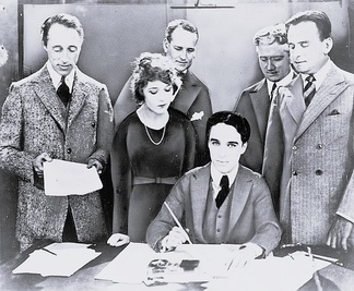 D. W. Griffith, Mary Pickford, Charlie Chaplin (seated) and Fairbanks at the signing of the contract establishing United Artists in 1919