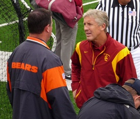 Pete Carroll talking to a pro scout before a game; during his tenure, 53 USC players were drafted by the NFL.