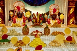 Annakut community meals (left), Krishna holding Govardhan ritually made from cow dung, rice and flowers (right).