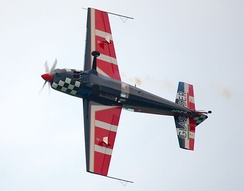 Extra 300L aircraft, from below, showing light coloured quadrilateral spades at roughly midwing.