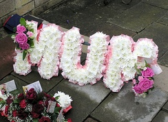 "A floral name tribute (spelling out the word ""Mum"") at a funeral in England."