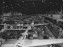 P-38 Lightning assembly line at the Lockheed plant, Burbank, California in World War II. In June 1943, this assembly line was reconfigured into a mechanized line, which more than doubled the rate of production. The transition to the new system was accomplished in only eight days. During this time production never stopped. It was continued outdoors.[11]