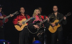 A blond woman sits on a long bar stool in front of a microphone playing a black acoustic guitar. The woman's hair is wavy and she wears a black dress with a number of pink threads around her neck. On her right two middle aged men playing acoustic guitar are visible.