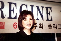 A close up photo of Regine Velasquez with a banner behind her bearing her name and some Korean text