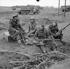 Reverend G B Fairhurst, Padre of the 2/5th Battalion, Queen's Royal Regiment, talking to two of the men in his battalion and an American soldier in the Anzio bridgehead, Italy, 20–21 February 1944.