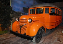 A 1939 school bus seen in a museum display. Its orange color predates the adoption of school bus yellow.