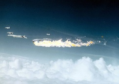The aircraft formation immediately following the collision; the F-104 has exploded, while the XB-70 is missing one of its vertical stabilizers. The F-4, F-5 and T-38 had yet to break formation.