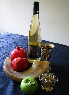 Rosh Hashana symbols: shofar, apples and honey, pomegranates, kiddush wine