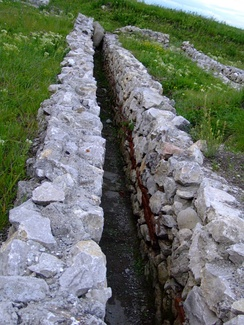 A sanitary channel at Potaissa, Dacia (modern Romania). It is placed cross-slope with a slight decline and then exits down-slope.