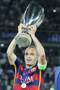 Iniesta lifting the 2015 UEFA Super Cup trophy.