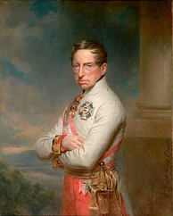 Half-length oil portrait of the Archduke Charles by Georg Decker. Charles wears a white high-collared military jacket of the Austrian army and has a red and white sash over his right shoulder. He wears two decorations, a cross on his breast and another medal at his neck. He has a long fleshy face, short brown hair, and light eyes, and gazes calmly towards the viewer. His arms are folded across his chest.