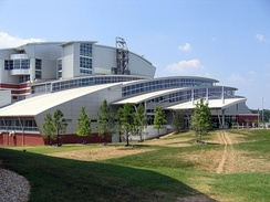 A large, white, multi-story building constructed from concrete, metal and glass with several tiered, curved roof segments framing long panels of windows. The building is set back on a large green lawn with several small pine trees.