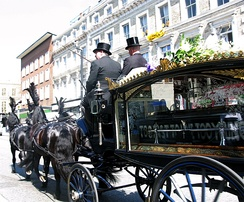Funeral directors driving a hearse in a funeral procession