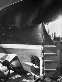 RMS Olympic's rudder with central and port wing propellers;[d] for scale note the man at the bottom of the photo.[37]