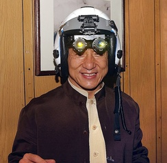 Jackie Chan tries on a fighter pilot's helmet with night vision goggles