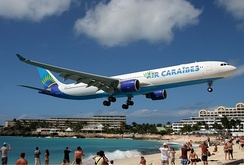 An Air Caraïbes Airbus A330-300 flying over Maho Beach shortly before touch-down