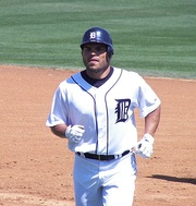 Man in a white baseball uniform and navy-blue helmet jogs on a baseball field