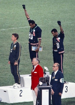 Gold medalist Tommie Smith (center) and bronze medalist John Carlos (right) showing the raised fist on the podium after the 200 m race at the 1968 Summer Olympics; both wear Olympic Project for Human Rights badges. Peter Norman (silver medalist, left) from Australia also wears an OPHR badge in solidarity with Smith and Carlos.