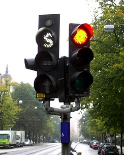 "Swedish traffic light (left) for use by public transport vehicles only. All signals use white lighting and special symbols (""S"", ""–"" and an arrow) to distinguish them from regular signals. The small light at the top tells the driver when the vehicle's transponder signal is received by the traffic light."
