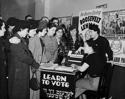 Women surrounded by posters in English and Yiddish supporting Franklin D. Roosevelt, Herbert H. Lehman, and the American Labor Party teach other women how to vote, 1936.