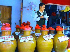 Locally produced crockery jars of baijiu in a liquor store in Haikou on Hainan, with signs indicating the alcohol content and price per jin (1/2 kilo).