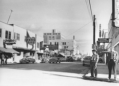 Photo taken by Elisabeth Meyer in 1955, looking easterly from Second Avenue and Cushman Street. The now-abandoned Polaris Building, the tallest building in Fairbanks since its completion in 1952, is in the background.