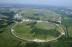 Aerial photo of the Tevatron at Fermilab, which resembles a figure eight. The main accelerator is the ring above; the one below (about half the diameter, despite appearances) is for preliminary acceleration, beam cooling and storage, etc.
