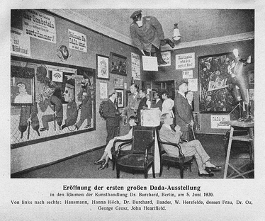 Grand opening of the first Dada exhibition: International Dada Fair, Berlin, 5 June 1920. The central figure hanging from the ceiling was an effigy of a German officer with a pig's head. From left to right: Raoul Hausmann, Hannah Höch (sitting), Otto Burchard, Johannes Baader, Wieland Herzfelde, Margarete Herzfelde, Dr. Oz (Otto Schmalhausen), George Grosz and John Heartfield.[1]