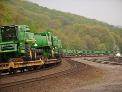 John Deere Combine harvesters being transported by railway on flat cars in Tyrone, Pennsylvania, in the United States.