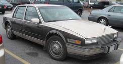 1988 Seville — the silver top half of the two-tone paint ties in with the bottom sides chrome cladding