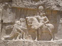 a relief cut into rocks depicting a man on horseback and two men, one standing and the other bowing in front of the horse rider