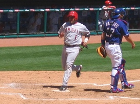 Bengie Molina of the Anaheim Angels (left) scores a run by touching home plate after rounding all the bases.