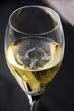 A glass of Champagne exhibiting the characteristic bubbles associated with the wine