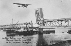 "The Grafton Bridge over the Clarence River showing Bascule span lifted to let shipping through. (Postcard from about 1932; The ""Southern Cross"" aeroplane has been added to the photograph.)"
