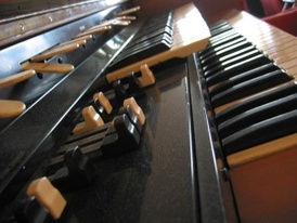 A close-up of the Hammond L-100 organ, with the drawbars in the foreground